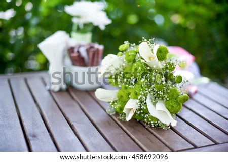 green white bridal bouquet on a wooden table - stock photo