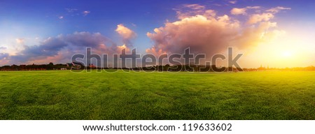 Green wide meadow with grass and colorful cloudy sky at sunset - stock photo