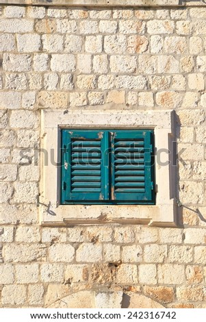 Green window with wood shutters closed on the facade of a stone house, Dubrovnik, Croatia - stock photo