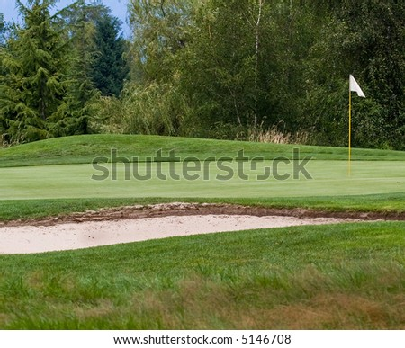green with sand trap in front of it - stock photo