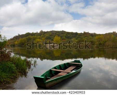 Green wooden boat on autumn river