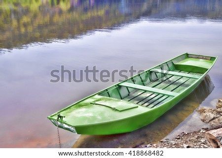 Green Wooden Boat Tied To A Small Dock On Calm Lake Against Shiny Background - stock photo