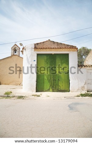 green wooden door and basic church at chinchilla albacete spain - stock photo