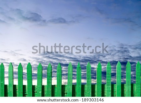 green wooden fence on a blue sky background
