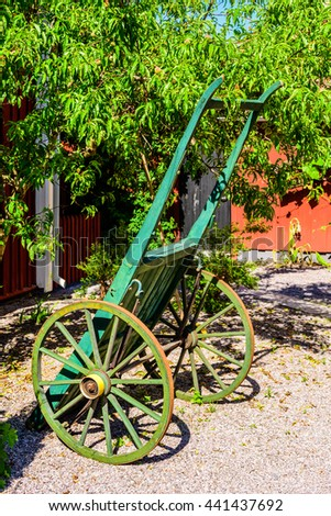 Green wooden handcart standing upright on gravel with a fruit tree in the background.