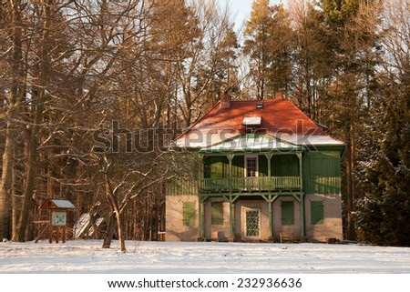 green wooden house Hummelshain - winter forest landscape - stock photo