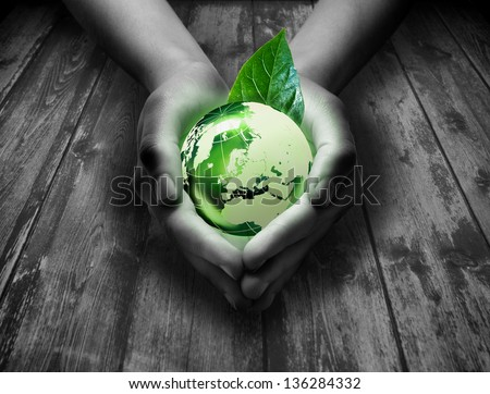 green world in the heart hand - wood background - stock photo