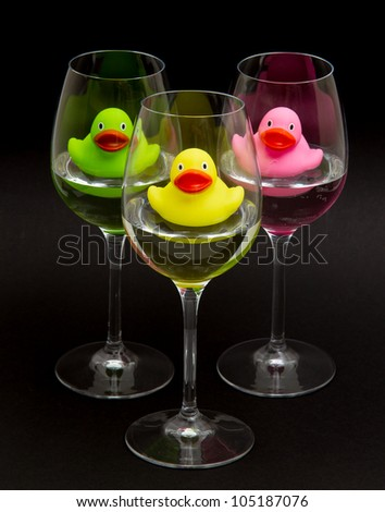 Green, yellow and pink rubber ducks in wineglasses, dark background - stock photo