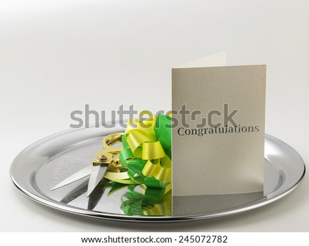 green yellow ribbon bows, scissors and a greeting card - stock photo