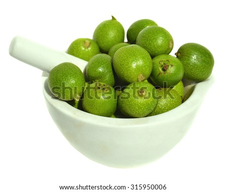 Green young walnuts in pounder on white background - stock photo