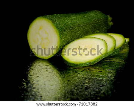 green zucchini with water drops on a black background - stock photo