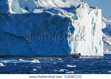 Greenland. Centuries-old thicknesses of glaciers. Boat in front of Icebergs Research of a phenomenon of global warming