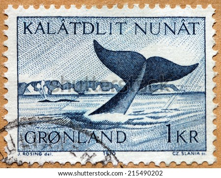 GREENLAND - CIRCA 1970: A stamp printed by DENMARK shows image of tail part of a whale above the surface of the sea, circa 1970 - stock photo