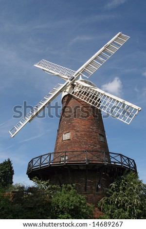 Greens Windmill in Nottingham UK. Red brick building with four white sails against a blue sky