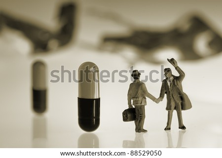 greeting between two miniature figures with capsules in the background - stock photo