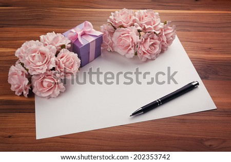 Greeting blank card with pen, pink roses and purple gift box - stock photo
