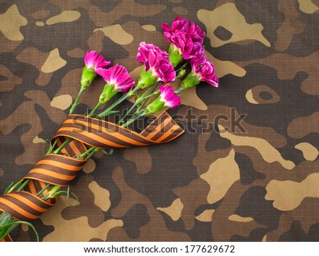 Greeting card design for military with flowers and St. George Ribbon on a camouflage background. - stock photo