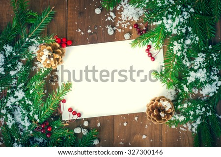 greeting card for the Christmas holidays . Spruce branches , cones and red berries covered with snow . Space for labels on a wooden surface . - stock photo