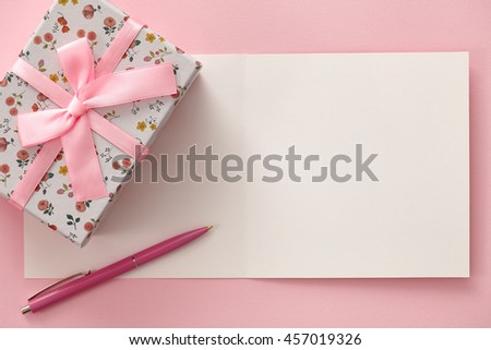 Greeting card, gift box and pen in pink colors - stock photo