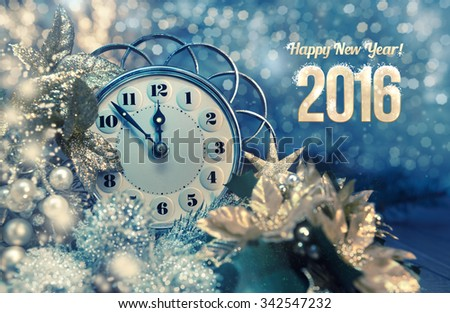 "Greeting card ""Happy New Year 2016!"" with vintage clock showing five to mignight and sparkling lights. This image is toned. Shallow DOF, focus on the clock arms and numbers - stock photo"