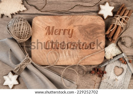 "Greeting card ""Merry Christmas"" burnt on wooden board with winter decorations around - stock photo"