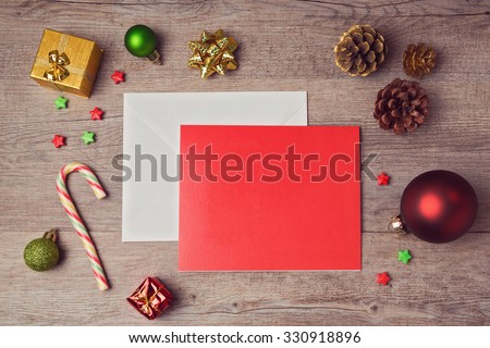Greeting card mock up template with Christmas decorations on wooden background. View from above - stock photo