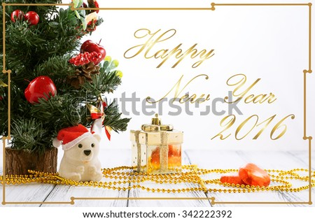 Greeting card with Christmas tree, gold gift box, balls, toy bear, candies and decorations on retro vintage white table isolated on white with golden ornament - stock photo