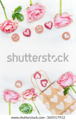 Greeting card with pink roses , chocolate heart,  paper shopping bag and text for you and with love on white wooden background, top view. Place for text, frame. Valentine Day or Birthday concept. - stock photo