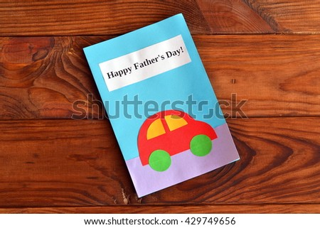 Greeting card with text Happy father's day and car applique. Greeting card on a wooden table. Father's day gift for kids to make. Original handmade gift. Home children paper diy - stock photo