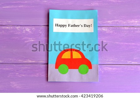 Greeting card with text. Happy father's day. Postcard isolated on purple wooden background. Paper greeting card children's modern crafts. Idea kids gift for dad.  - stock photo