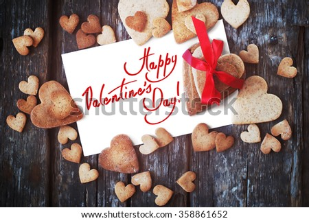 Greeting card with text Happy Valentine's Day on the White Isolated Letter and Gingerbread Cookies in the Shape of Heart on Wooden Table. Selective focus - stock photo
