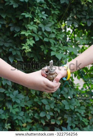 grenade in the hands of children. Social Poster - stock photo