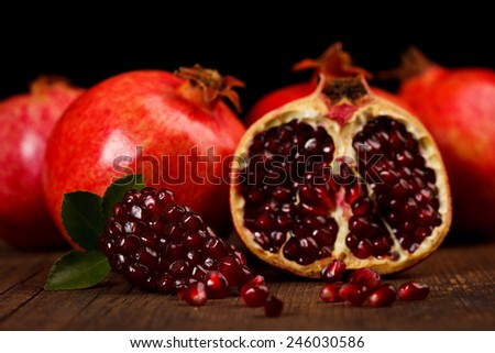 Grenadine fruits and seeds with small green leaf on rustic wooden table - stock photo
