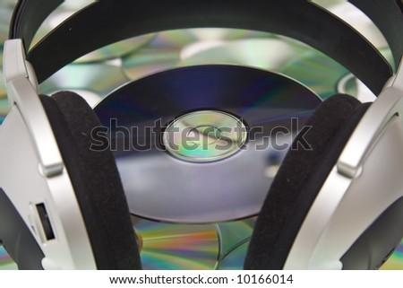 Grey and black earphones and compact disc