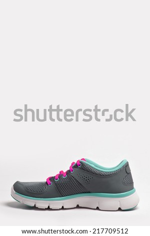 grey and emerald green and magenta(purple) running shoes side view isolated white. - stock photo