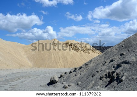 Grey and yellow sand mound and blue sky - stock photo