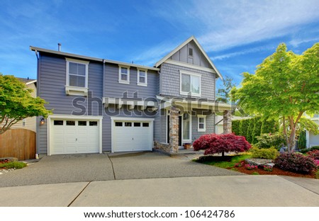 Grey classic house with two white garage doors. - stock photo