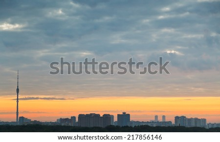 grey clouds and yellow sunrise sky over city, Moscow - stock photo