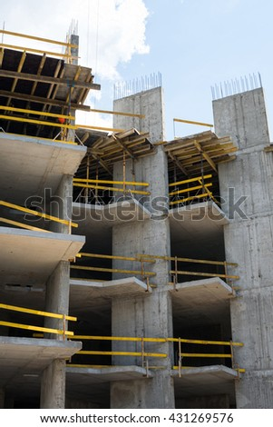 Grey concrete framework of the future building in the construction site - stock photo