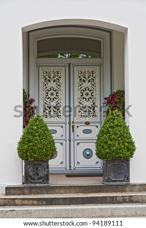 Grey double door with plants in flower pots on the stairs. Shot from Friedrichstadt, Germany