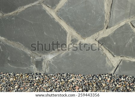 Grey flagstone wall with gravel pathway. Background photo. Random stone pattern wall. Grey house wall. Pavement pattern. Flat stone elements. Residential building with natural stone wall exterior. - stock photo