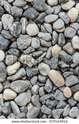 grey flecked river rocks piled together. Polished rocks and pebbles in a dry stream - stock photo