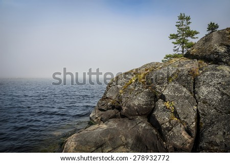 grey granite cliff in the water - stock photo