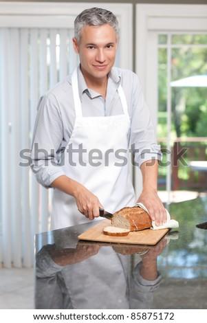 Grey hair man cutting bread in apron - stock photo