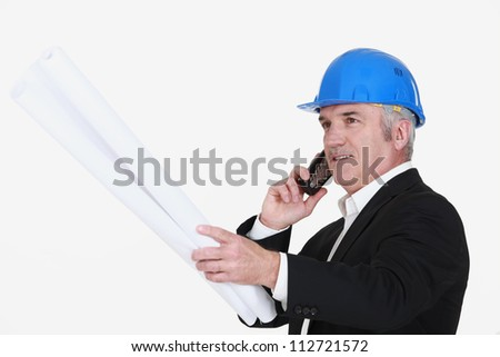 Grey-haired architect with plans - stock photo