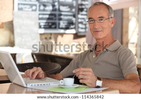 Grey-haired man in coffee shop - stock photo