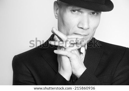 Grey-haired man in hat and suit at the age of forty-six years old  with hands to head support  looking at the camera on black background - stock photo