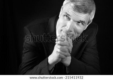 Grey-haired man in suit at the age of forty-six years old  with hands to head support on black background - stock photo