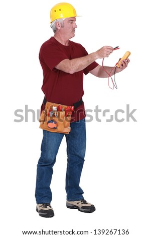 Grey-haired man using voltmeter - stock photo