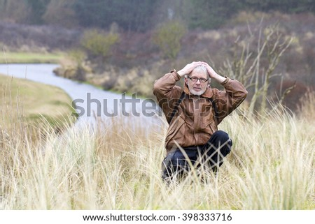 Grey Haired Older Man with Glasses and Brown Leather Jacket Sitting in a Nature Background with His Hands on His Head - stock photo